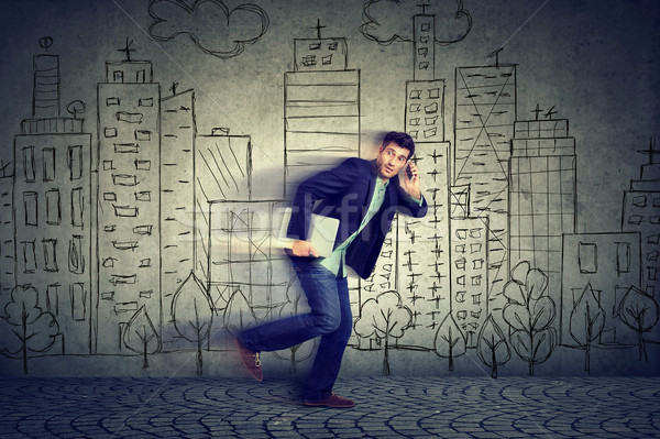 Stock photo: Young man running late to work talking on mobile phone