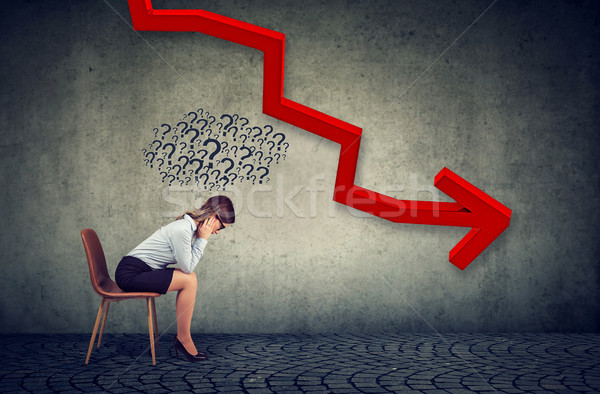 Depressed businesswoman looking down at the falling arrow feeling confused has many questions Stock photo © ichiosea