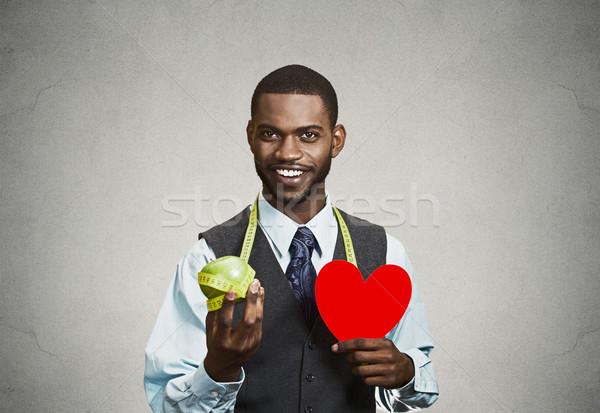 Closeup portrait, headshot business man, corporate executive holding green apple, red heart measurin Stock photo © ichiosea
