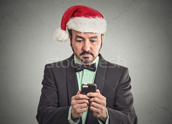 man in santa claus hat looking at smartphone searching online deal  Stock photo © ichiosea