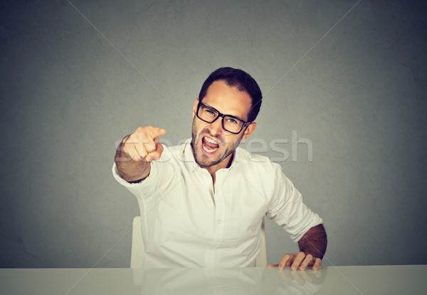 Angry businessman sitting at his desk and screaming Stock photo © ichiosea