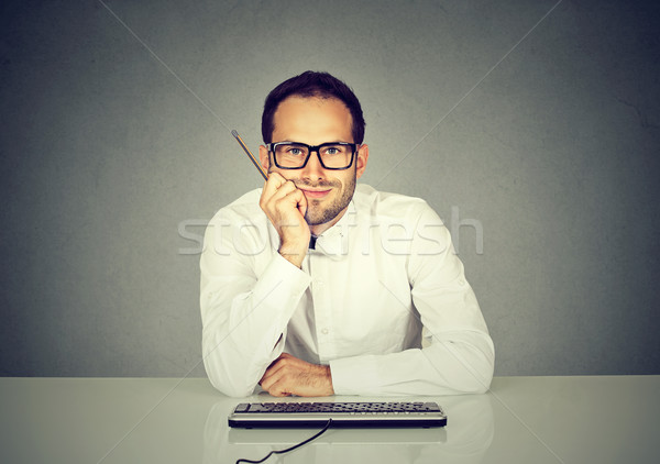 Smiling young handsome man sitting in front of computer keyboard Stock photo © ichiosea