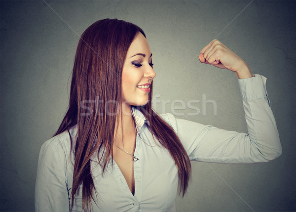Young happy woman flexing muscles showing her strength Stock photo © ichiosea