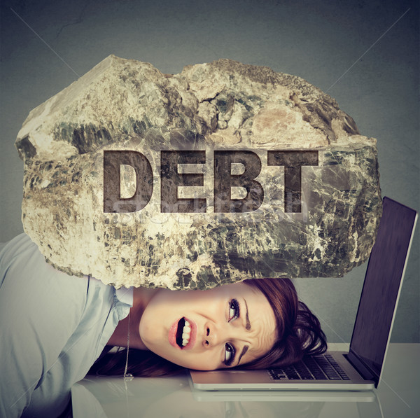 business woman with head squeezed between laptop and a rock Stock photo © ichiosea