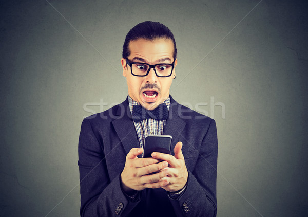 Amazed man browsing smartphone Stock photo © ichiosea