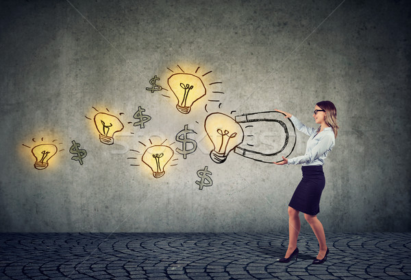 Businesswoman attracts bright ideas light bulbs with a big magnet Stock photo © ichiosea
