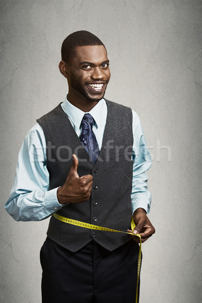 Happy man measuring his waist with tape Stock photo © ichiosea