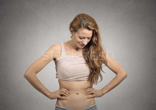 girl looks at her abdomen with concerned face expression Stock photo © ichiosea