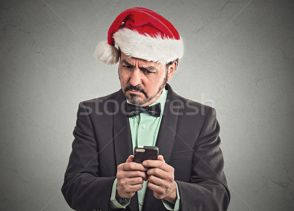 skeptical man wearing santa claus hat looking at smartphone  Stock photo © ichiosea
