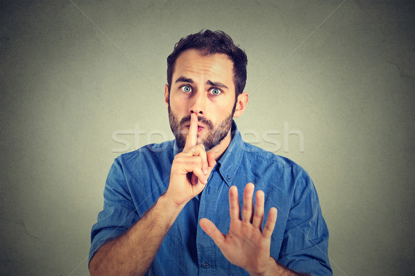 man giving Shhhh quiet, silence, secret gesture isolated on gray wall background   Stock photo © ichiosea