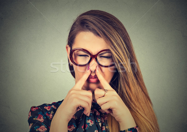 woman pinches nose with fingers looks with disgust bad smell Stock photo © ichiosea