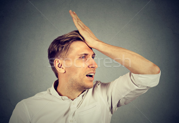 silly man, slapping hand on head having duh moment regrets  Stock photo © ichiosea