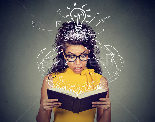 Surprised woman reading a book captivated by an unexpected plot twist Stock photo © ichiosea
