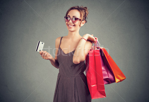 Beautiful young woman in sunglasses with shoppping bags and credit card  Stock photo © ichiosea