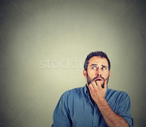nervous stressed young man student biting fingernails looking up  Stock photo © ichiosea