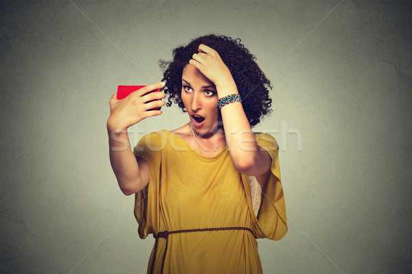 unhappy frustrated young woman surprised she is losing hair, receding hairline Stock photo © ichiosea