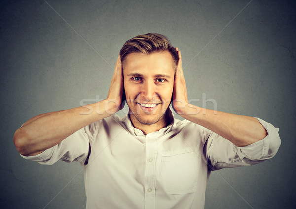 Handsome happy young man covering his ears  Stock photo © ichiosea