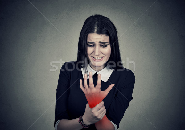 Young woman holding her painful wrist colored in red. Sprain pain Stock photo © ichiosea