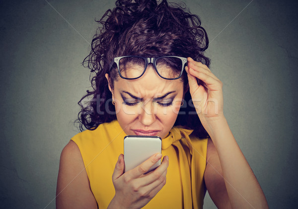 woman with glasses having trouble seeing cell phone vision problems Stock photo © ichiosea