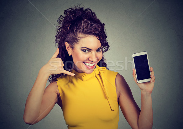 Pretty woman holding mobile phone showing call me hand gesture  Stock photo © ichiosea