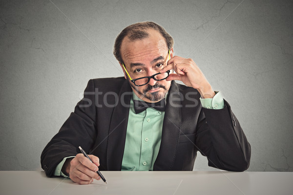 man with glasses skeptically looking at you sitting at his desk  Stock photo © ichiosea