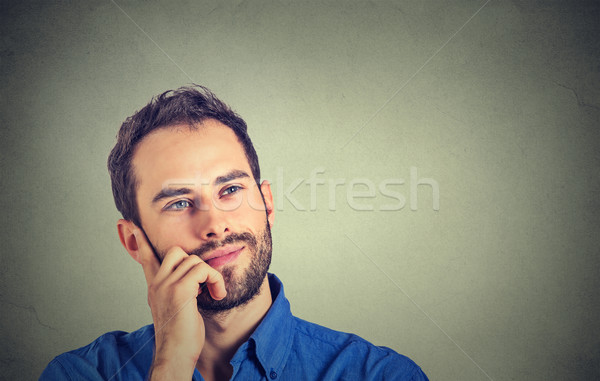 Happy young man thinking daydreaming looking up isolated on gray wall background  Stock photo © ichiosea