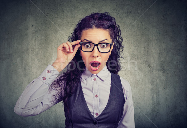 Shocked woman in glasses looking at camera Stock photo © ichiosea