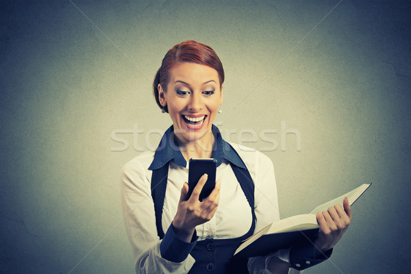 happy young woman holding book looking at phone seeing good news Stock photo © ichiosea
