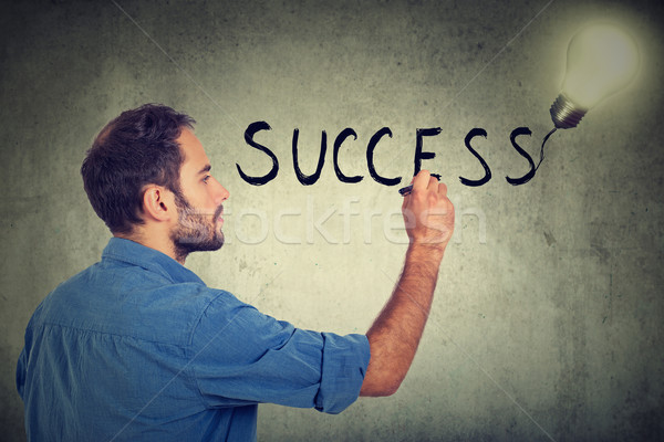 Side profile young man writing success on a gray wall Stock photo © ichiosea