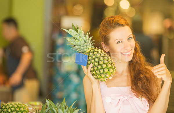 Happy young woman with pineapple smiling healthy and joyful in grocery shop  Stock photo © ichiosea