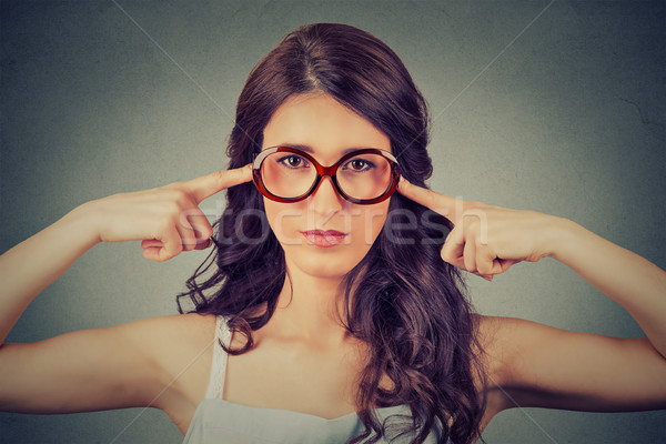 Nerdy woman in glasses plugging ears with fingers doesn't want to listen Stock photo © ichiosea