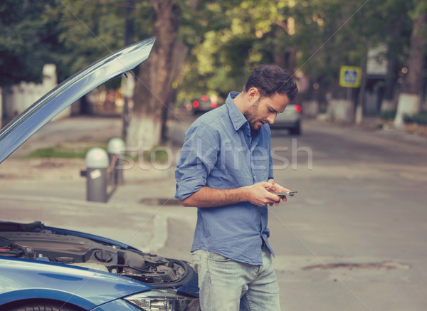 Upset man texting roadside assistance after breaking down Stock photo © ichiosea
