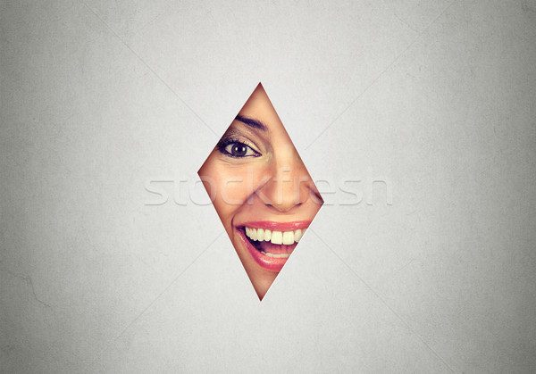 Portrait of a surprised woman laughing looking though the gap in background at camera  Stock photo © ichiosea