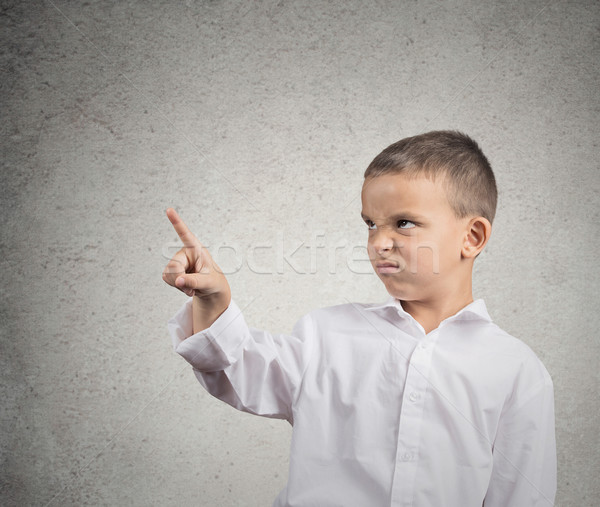 Unhappy boy pointing with finger at copy space Stock photo © ichiosea