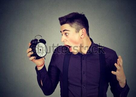 angry young man screaming at alarm clock, running late Stock photo © ichiosea