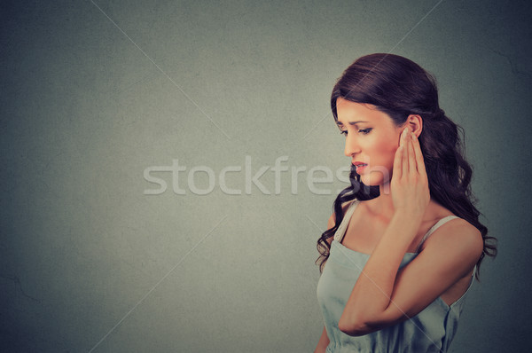 Tinnitus. Side profile sick young woman having ear pain touching her painful head  Stock photo © ichiosea