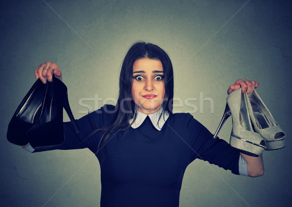 Perplexed woman keeps two stylish pumps can't choose one for her Stock photo © ichiosea