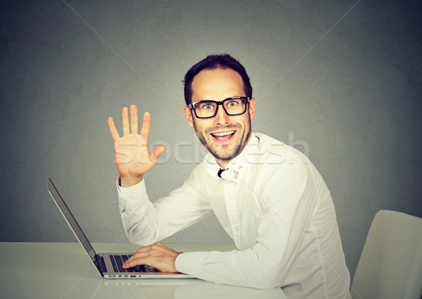 Man with laptop waving with hand saying hi to camera  Stock photo © ichiosea