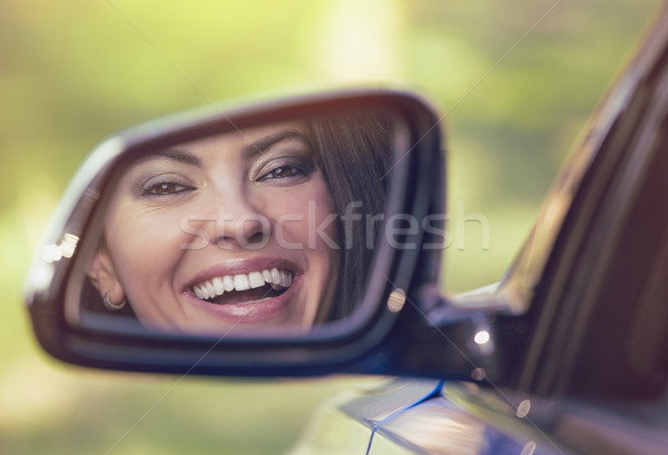 Happy woman driver looking in car side view mirror laughing  Stock photo © ichiosea