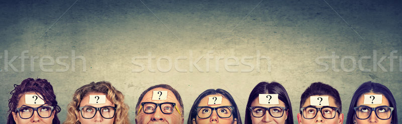 Stock photo: Multiethnic group of thinking people in glasses with question mark looking up