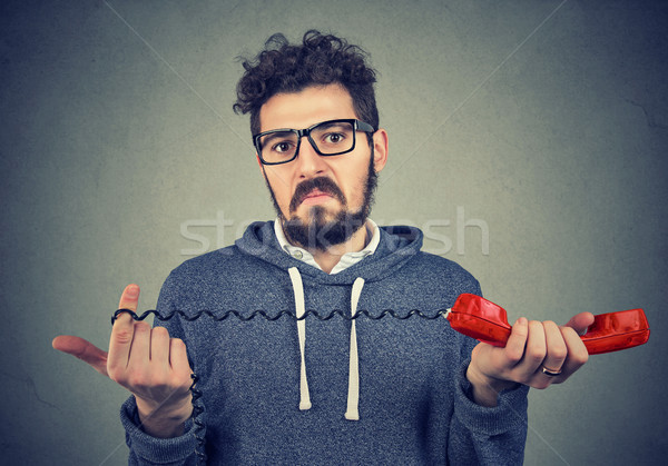Disgusted man looking at camera with confusion holding old fashioned red handset.  Stock photo © ichiosea