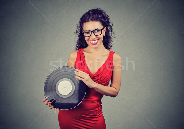 Smiling beautiful young woman showing a vintage vinyl Stock photo © ichiosea