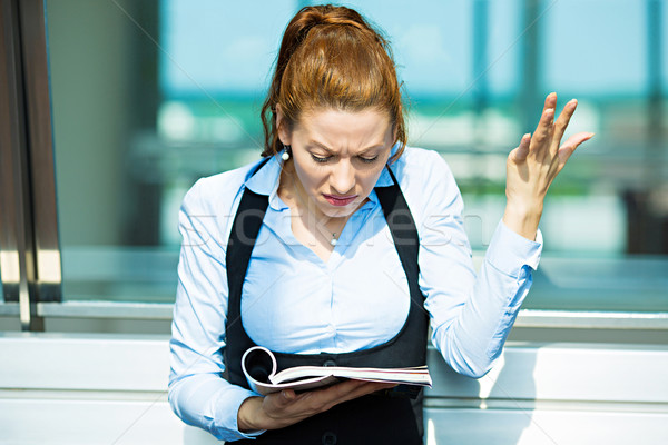 Stock photo: Business woman reading magazine, confused