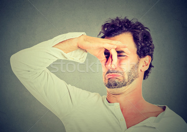 man with disgust on face pinches nose, something stinks bad smell  Stock photo © ichiosea