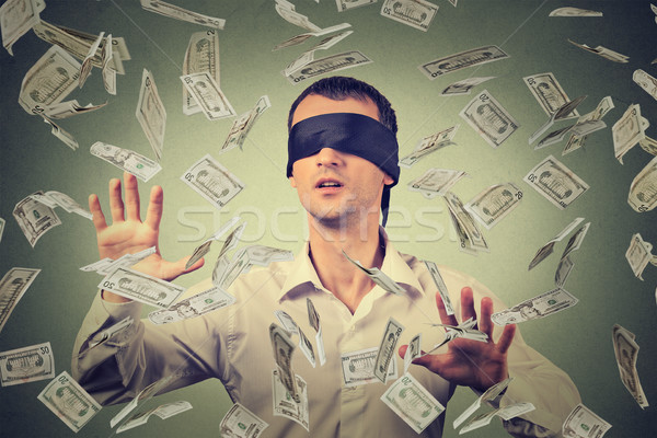 Blindfolded young businessman trying to catch dollar bills banknotes flying in air Stock photo © ichiosea