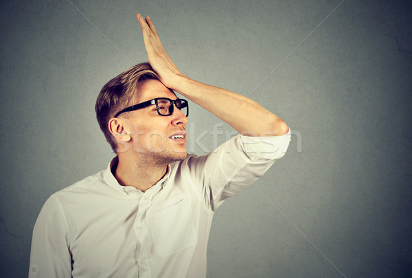 Silly man slapping hand on head having duh moment Stock photo © ichiosea