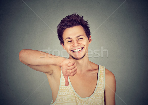 Sarcastic happy young man showing thumbs down hand gesture Stock photo © ichiosea