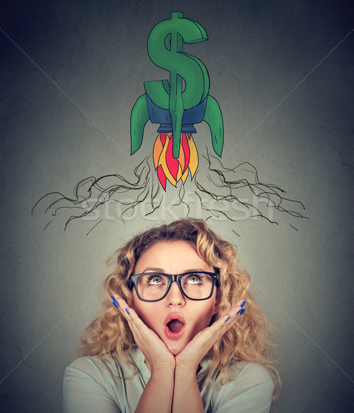 Surprised young woman in glasses looking up dollar sign above head  Stock photo © ichiosea