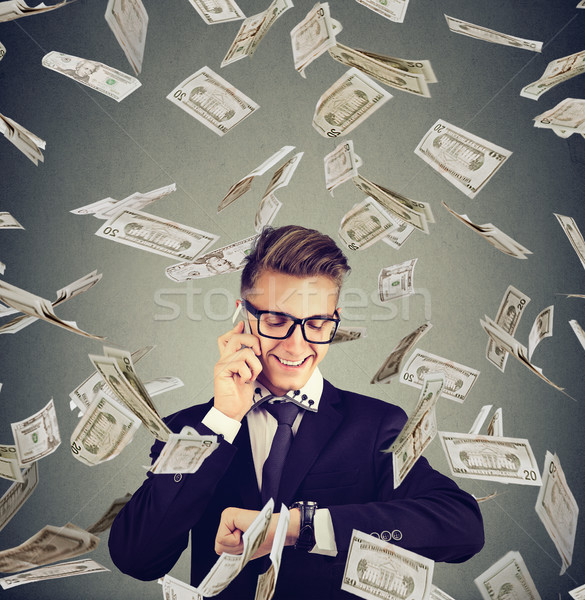 Busy businessman looking at wrist watch, talking on mobile phone under cash rain. Time is money conc Stock photo © ichiosea