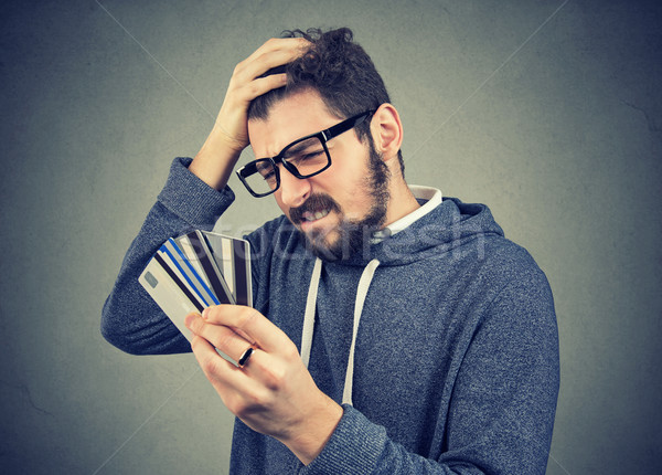 stressed man looking at too many credit cards Stock photo © ichiosea